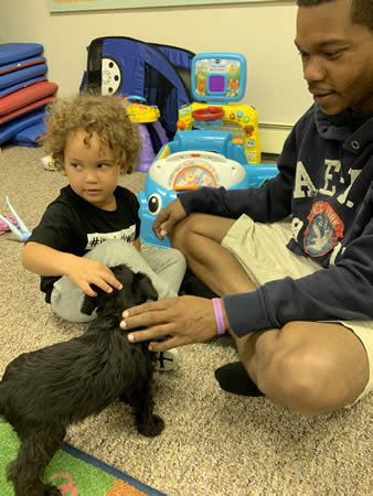 Dad & child playing with puppy during visitation